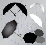 Siluette degli ombrelli nei precedenti delle gocce di pioggia Immagine Stock