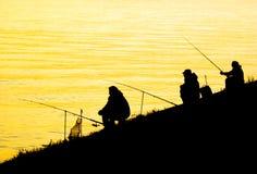 Siluette degli uomini di pesca Immagine Stock
