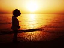 Siluette dei bambini alla spiaggia Immagine Stock