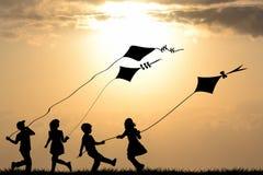 Siluette dei bambini che giocano con gli aquiloni immagini stock libere da diritti
