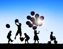 Siluette dei bambini che giocano i palloni e che guidano bicicletta Fotografia Stock