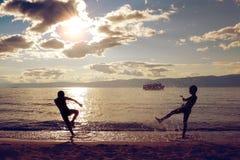 Siluette dei bambini che giocano sul tramonto Fotografie Stock Libere da Diritti