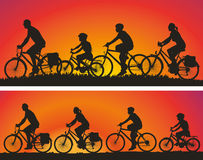 Siluette dei ciclisti sui precedenti dei tramonti Immagini Stock