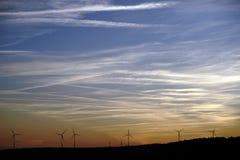 Siluette dei generatori eolici davanti al cielo uguagliante fotografia stock