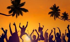 Siluette dei giovani che fanno festa su una spiaggia fotografie stock