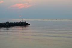 Siluette dei pescatori sul frangiflutti ad alba Fotografia Stock Libera da Diritti
