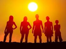 Siluette dei ragazzi e delle ragazze sulla spiaggia Fotografia Stock