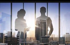 Siluette dei soci commerciali sopra l'ufficio di città Immagini Stock Libere da Diritti