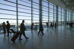Siluette dei viaggiatori e del personale dell'industria aerea che camminano nell'aeroporto internazionale di Newark, New Jersey Fotografia Stock Libera da Diritti