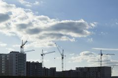 Siluette del cantiere con le costruzioni e le gru non finite contro il cielo con le nuvole fotografia stock libera da diritti