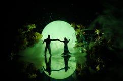 Siluette del dancing delle coppie del giocattolo sotto la luna alla notte Figure dell'uomo e della donna nel dancing di amore all Immagine Stock Libera da Diritti