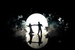 Siluette del dancing delle coppie del giocattolo sotto la luna alla notte Figure dell'uomo e della donna nel dancing di amore all Immagini Stock Libere da Diritti