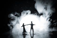 Siluette del dancing delle coppie del giocattolo sotto la luna alla notte Figure dell'uomo e della donna nel dancing di amore all Immagine Stock