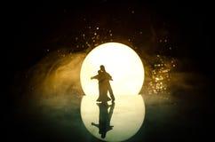 Siluette del dancing delle coppie del giocattolo sotto la luna alla notte Figure dell'uomo e della donna nel dancing di amore all Fotografia Stock Libera da Diritti