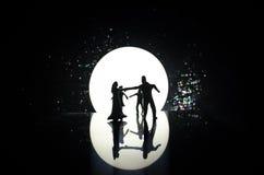 Siluette del dancing delle coppie del giocattolo sotto la luna alla notte Figure dell'uomo e della donna nel dancing di amore all Fotografie Stock