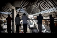 Siluette del ` dei viaggiatori alla stazione ferroviaria immagine stock