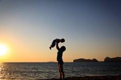 Siluette del figlio e del padre alla spiaggia fotografie stock