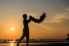 Siluette del figlio e del padre alla spiaggia fotografie stock libere da diritti