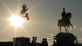 Siluette del monumento, gruppo di persone sotto e motociclisti di salto estremi video d archivio