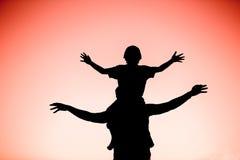 Siluette del padre e del figlio divertendosi insieme fotografia stock libera da diritti
