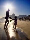 Siluette del tramonto brasiliano della spiaggia di Ipanema del bambino e del padre Fotografia Stock