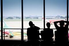 Siluette dell'uomo d'affari e dei passeggeri che viaggiano sull'aeroporto, Fotografia Stock Libera da Diritti