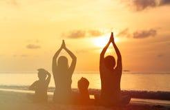 Siluette della famiglia che fanno yoga al mare di tramonto Fotografie Stock