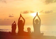 Siluette della famiglia che fanno yoga al tramonto fotografia stock