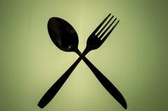 Siluette della forchetta e del cucchiaio attraversati immagine stock libera da diritti