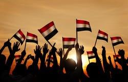 Siluette della gente che tiene la bandiera dell'Egitto Immagine Stock