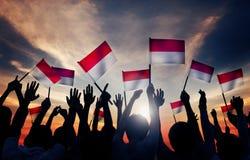 Siluette della gente che tiene la bandiera dell'Indonesia Immagini Stock