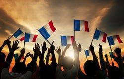 Siluette della gente che tiene la bandiera della Francia Fotografia Stock