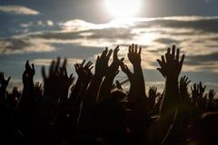 Siluette della gente con le mani su sollevate di un essere umano immagini stock