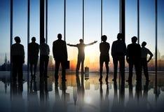 Siluette della gente di affari in un edificio per uffici fotografia stock