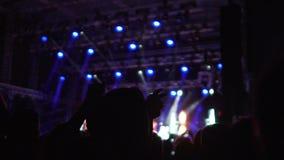 Siluette della gente felice che gode della musica al concerto, mani d'ondeggiamento in aria stock footage