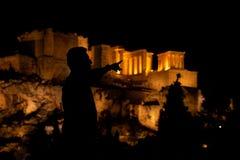 Siluette della gente nella priorità alta, con la vista di notte dell'acropoli ai precedenti fotografia stock