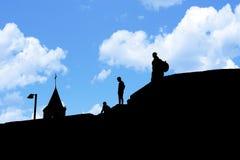 Siluette della gente sul tetto delle case Fotografie Stock