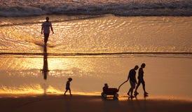 Siluette della gente sulla spiaggia fotografia stock