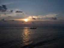 Siluette della gente in un kajak nei raggi del tramonto contro lo sfondo delle nuvole fotografia stock
