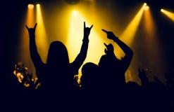 Siluette della gente in un luminoso nel concerto rock di schiocco davanti alla fase Mani con i corni di gesto Quello oscilla Part Fotografie Stock Libere da Diritti