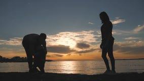 Siluette della madre e del padre che insegnano al loro neonato a come camminare il bambino della famiglia della siluetta impara c stock footage