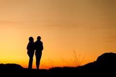 Siluette della madre e della figlia al bello tramonto dusk fotografie stock libere da diritti