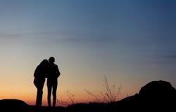 Siluette della madre e della figlia al bello tramonto dusk fotografia stock libera da diritti