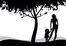 Siluette della madre e della figlia che guardano all'orizzonte sotto un albero Immagine Stock