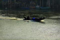 Siluette delle barche che pescano in acqua corrente fotografia stock