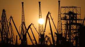 Siluette delle gru del porto al tramonto Porta del carico immagine stock libera da diritti