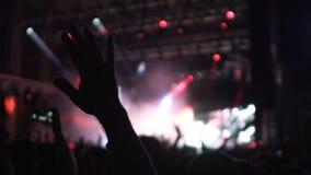 Siluette delle mani d'ondeggiamento della folla nell'euforia dalla prestazione dalla banda popolare stock footage