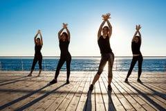 Siluette delle ragazze allegre che ballano sport vicino al mare all'alba Fotografia Stock