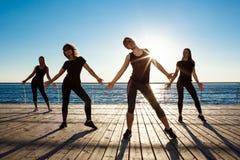 Siluette delle ragazze allegre che ballano vicino al mare all'alba Fotografie Stock