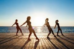 Siluette delle ragazze allegre che ballano vicino al mare all'alba Fotografie Stock Libere da Diritti